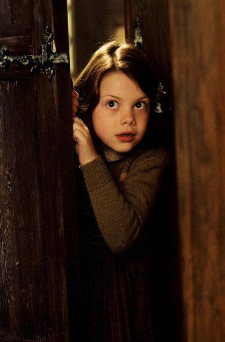 Escena de la película las crónicas de narnia lucy asomándose por una puerta