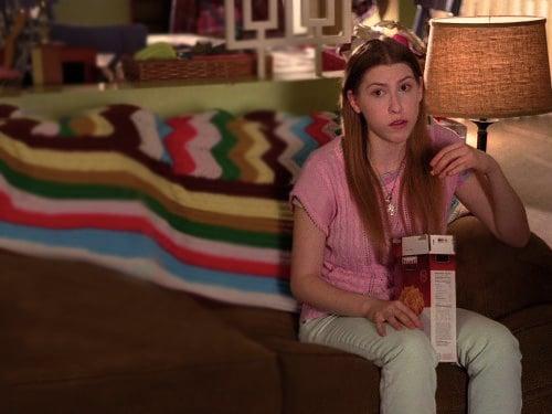 Chica sentada en un sofá comiendo una caja de galletas