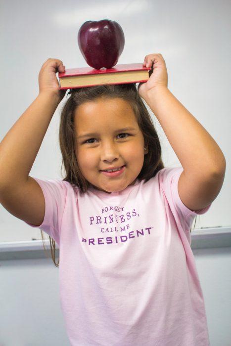 niña con libro en la cabeza y playera con mensaje