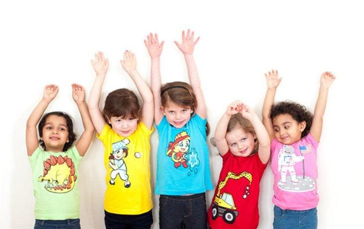 niños pequeños levantan las manos