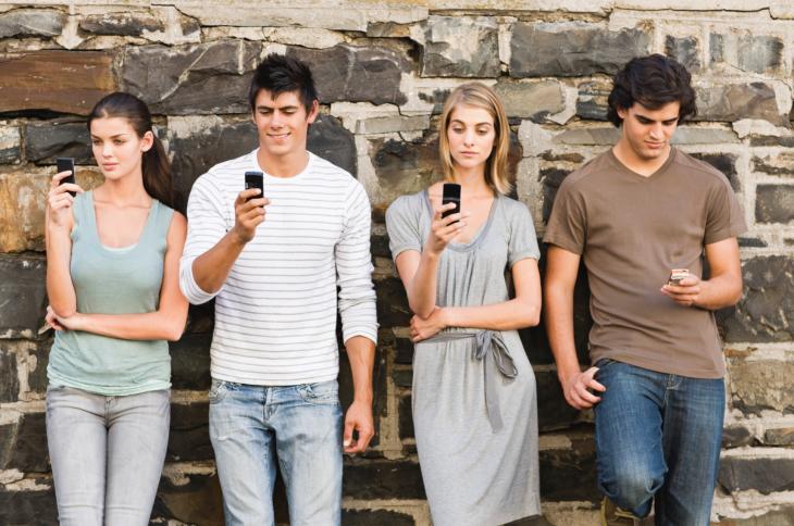 Grupo de chicos recargados en una pared con celulares en las manos