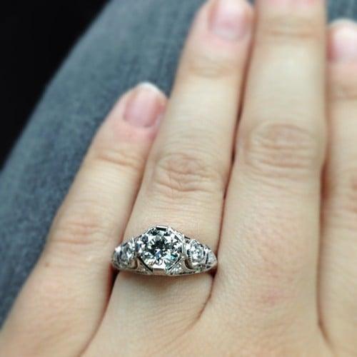 mano con anillo de compromiso de tres piedras
