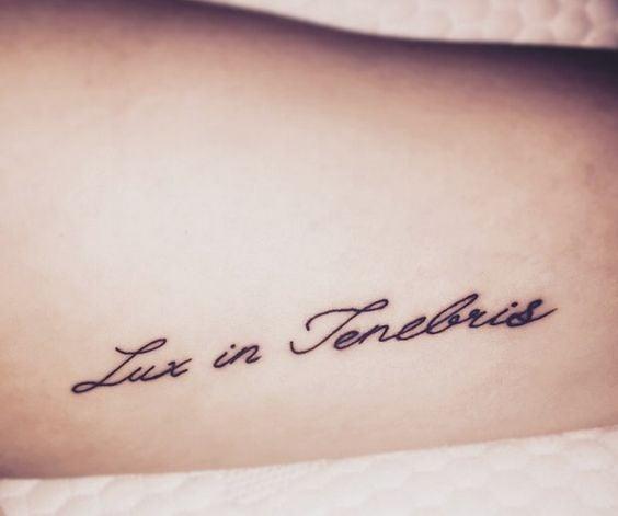Chica con un tatuaje que dice lux in tenebris