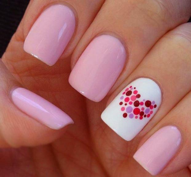 Uñas decoradas con esmalte color rosa y un corazón hecho con puntos de colores