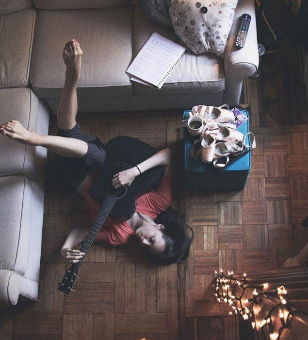 chica tocando guitarra en el suelo