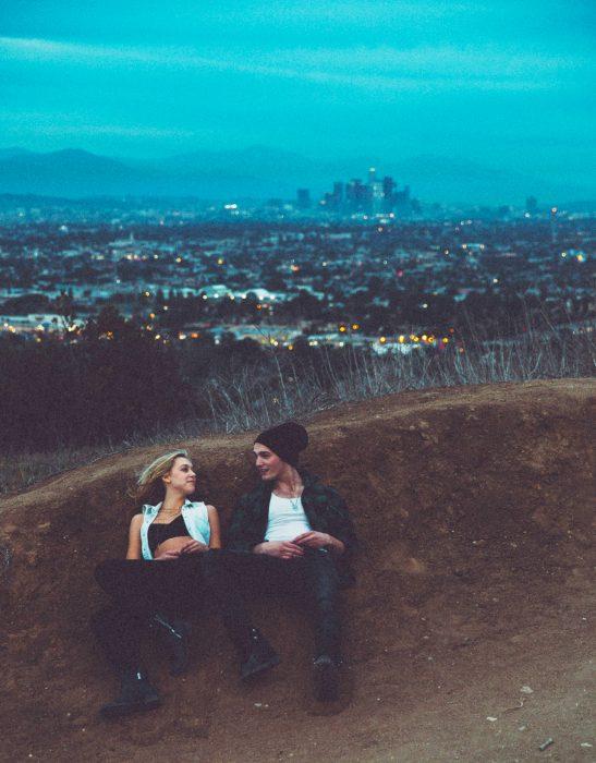 Pareja de novios sentados recargados en un monticulo de tierra