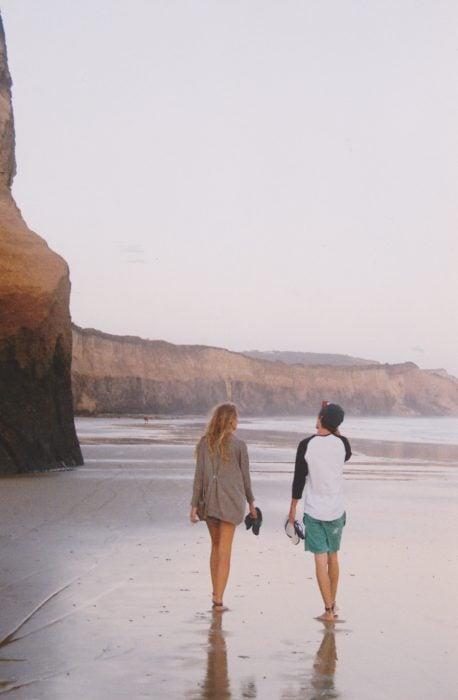 Pareja de novios caminando por la playa