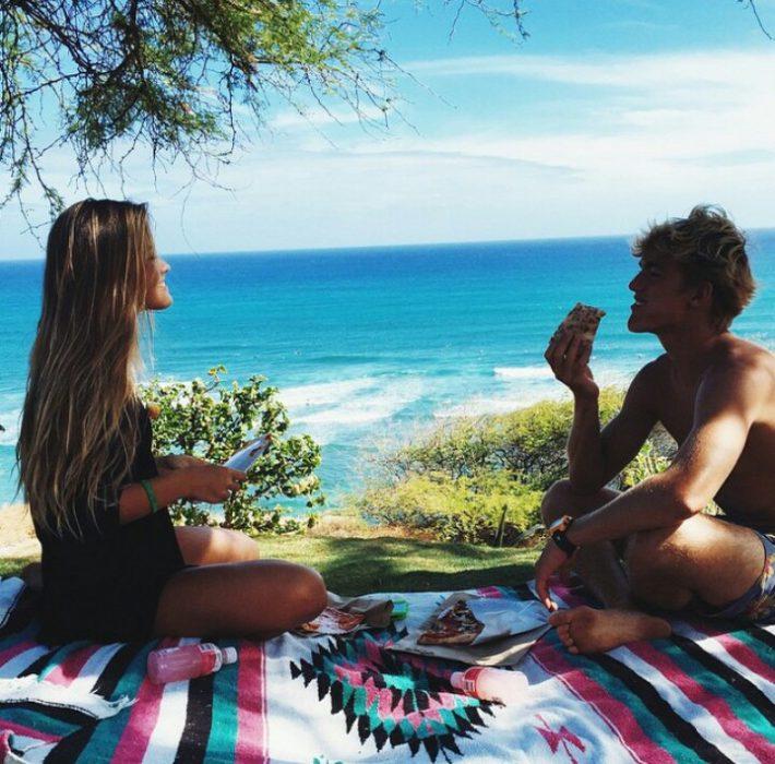 Pareja de novios sentados sobre una manta en un picnic