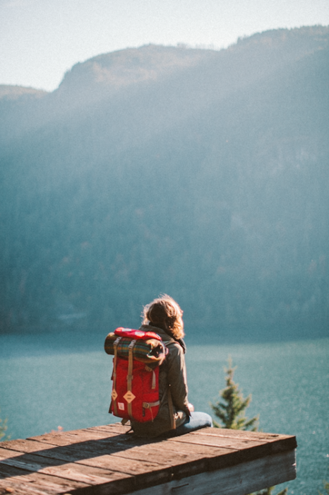 chica con mochila sentada frente a un lago