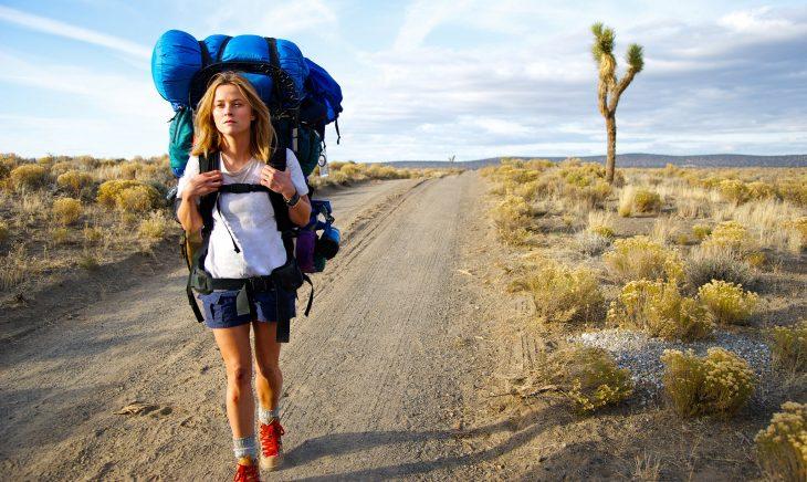 chica caminando por carretera con backpack