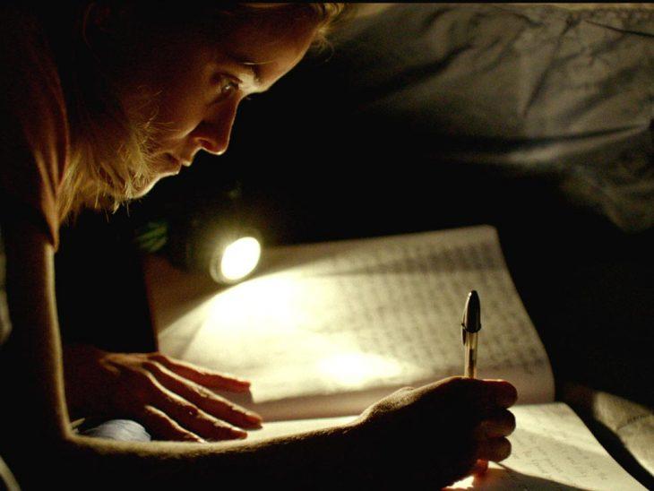 chica escribiendo a oscuras en casa de campaña