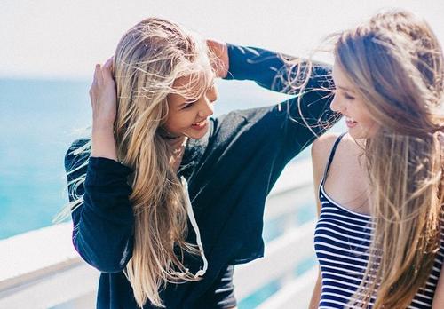 Chicas sentadas en un muelle conversando