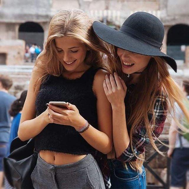 Chicas revisando un teléfono celular mientras están en la calle