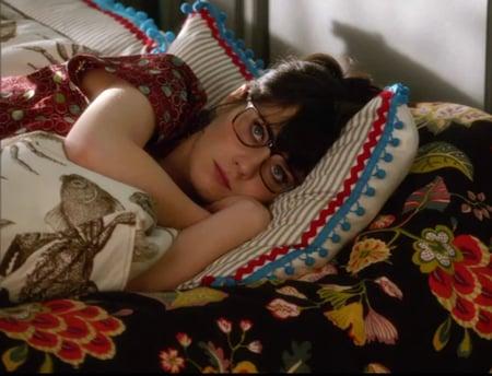 Zoey dechanel recostada en una cama intentando dormir