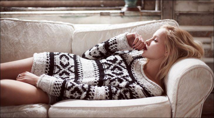 Chica recostada en un sofá intentando dormir