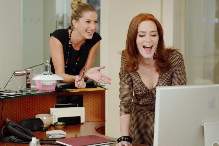 Escena de la película el diablo viste a la moda chicas riendo frente a una computadora