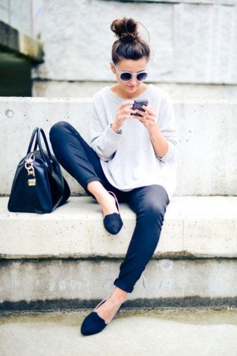 Chica revisando su telefono celular mietras está sentada en una banca