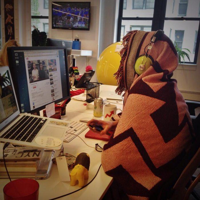 Chica en la oficina tapada con un cobertor