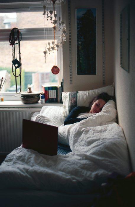 Chica recostada en una cama viendo su computadora