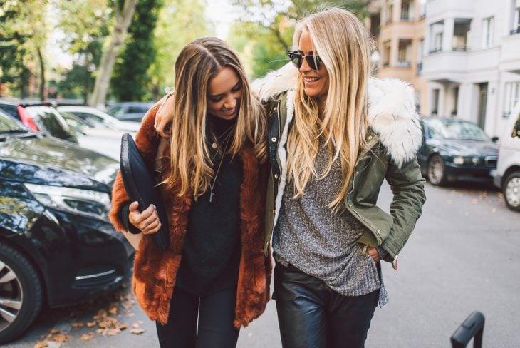 Chicas caminando por la calle abrazadas