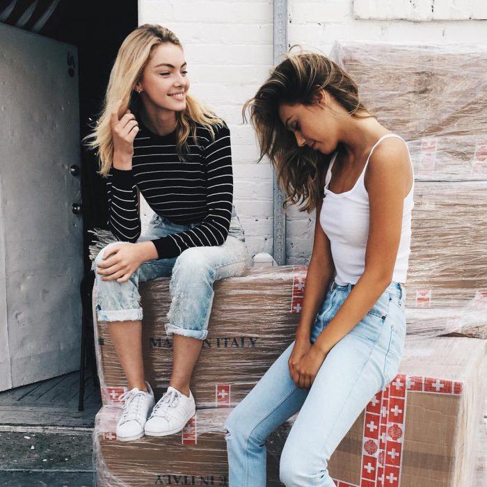Chicas sentadas sobre unas cajas conversando