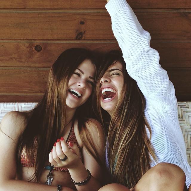 Amigas sentadas en una cama conversando y riendo