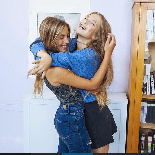 Amigas abrazadas y riendo en una casa