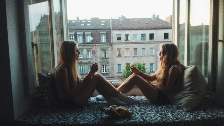 Mejores amigas sentadas frente a una ventana conversando