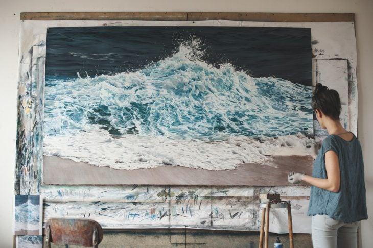 Chica pintando olas en un cuadro