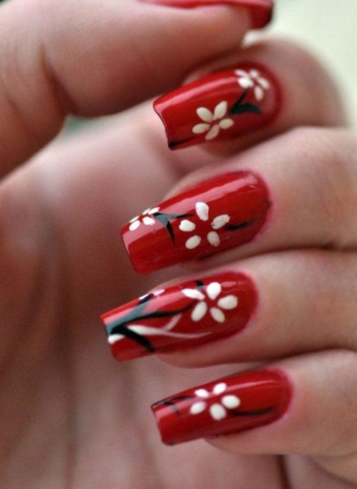 manicure rojo con flores blancas