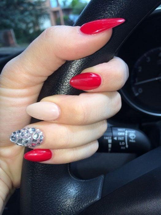 manicure rojo con uña pedrería y color piel forma almendrada