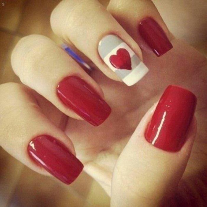 manicure rojo con una uña de corazón