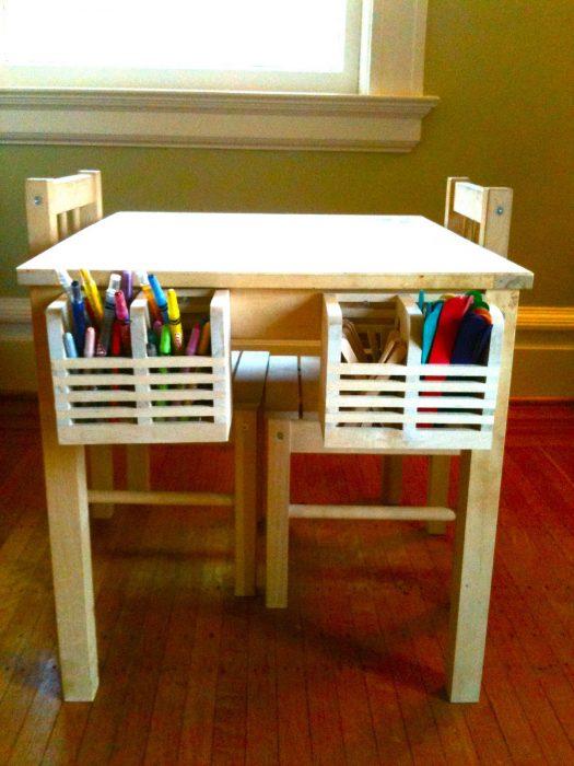Mesa para niños con dos cajas colocadas en el interior que contienen lapices