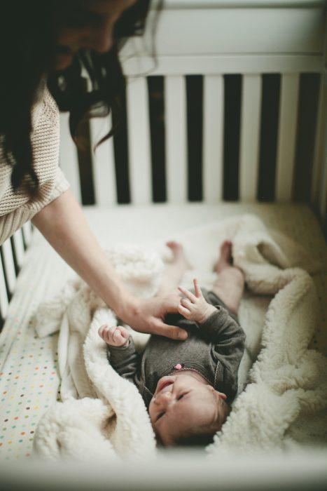 Mamá viendo a un bebé en su cuna