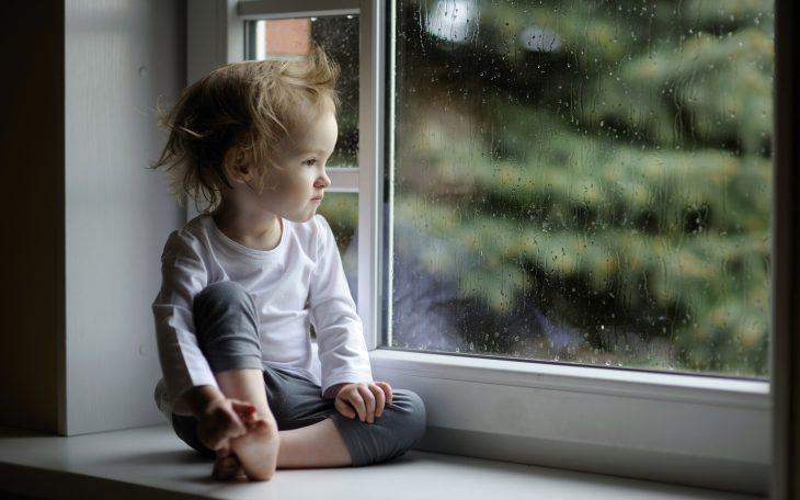 Bebé sólo sentado cerca de la ventana viendo el jardín