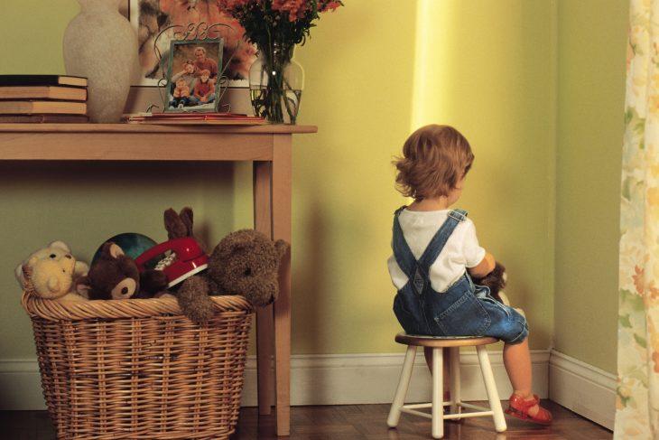 Bebé sentada en un banco frente a la pared