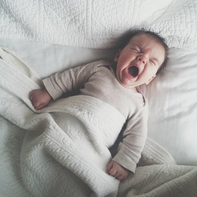 Bebé recostado en la cama llorando