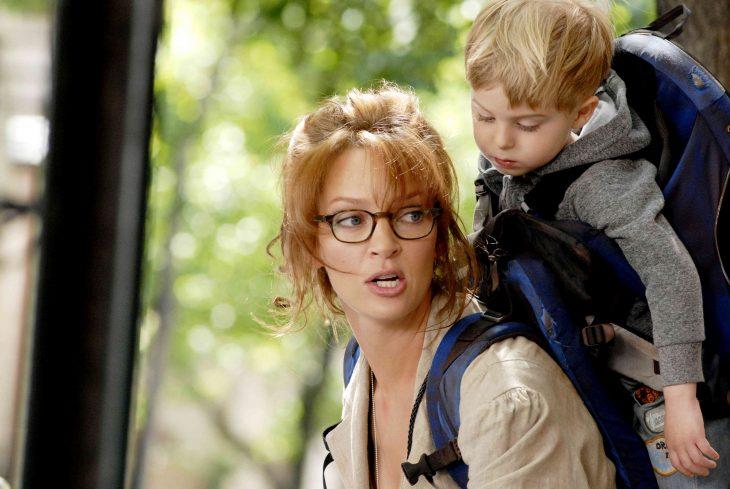 Mamá llevando a su hijo en la espalda-escena de Motherood