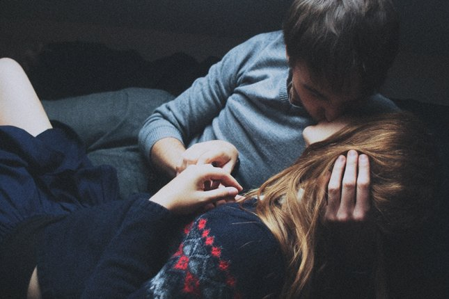 pareja besándose en un sillón