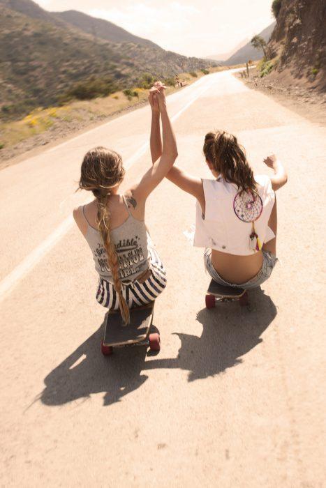 Chicas sentadas en una patineda deslizándose por la calle