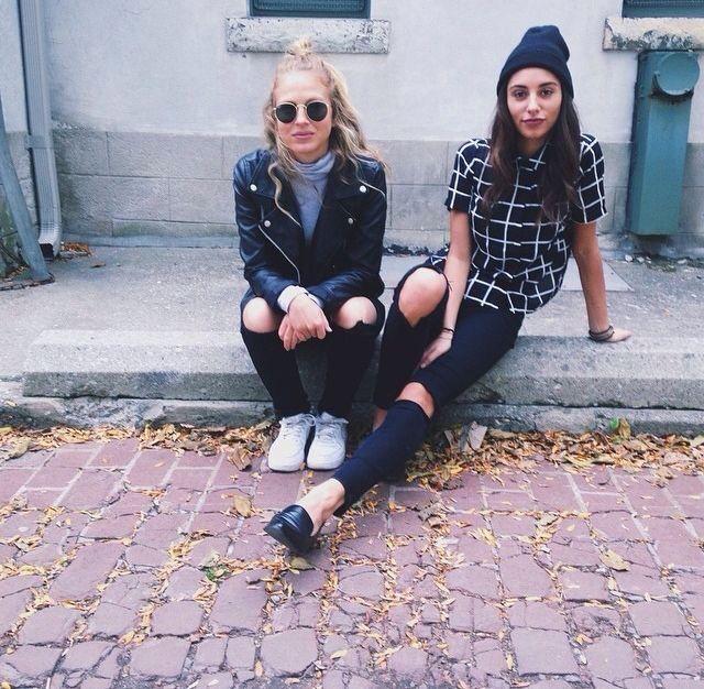 Chicas vestidas de negro sentadas en la acera de una calle