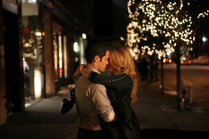 Pareja de novios abrazados y besándose en medio de la calle