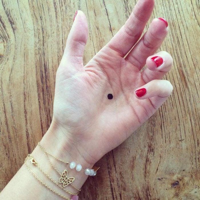 Mano con un punto negro en medio de la palma