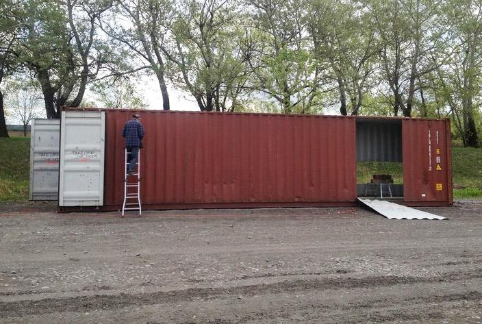 Persona cortando contenedores para construir una casa