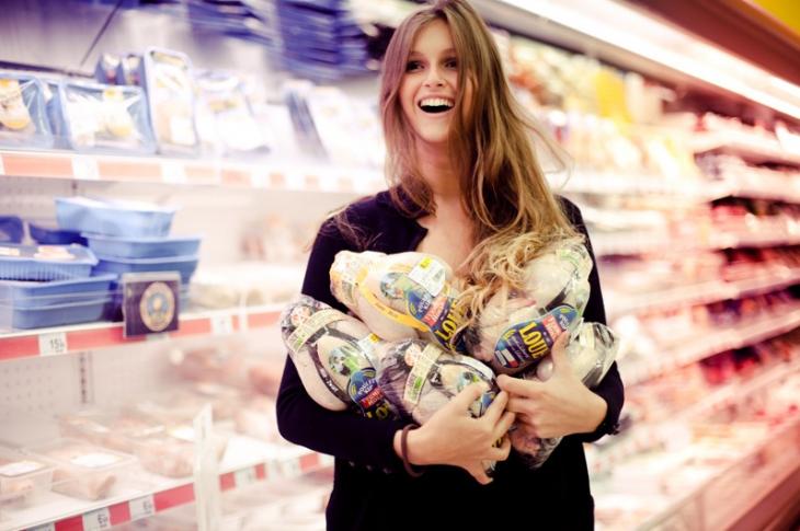 Chica en el supermercado cargando pavos