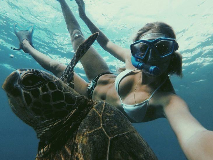 Chica nadando junto a una tortuga