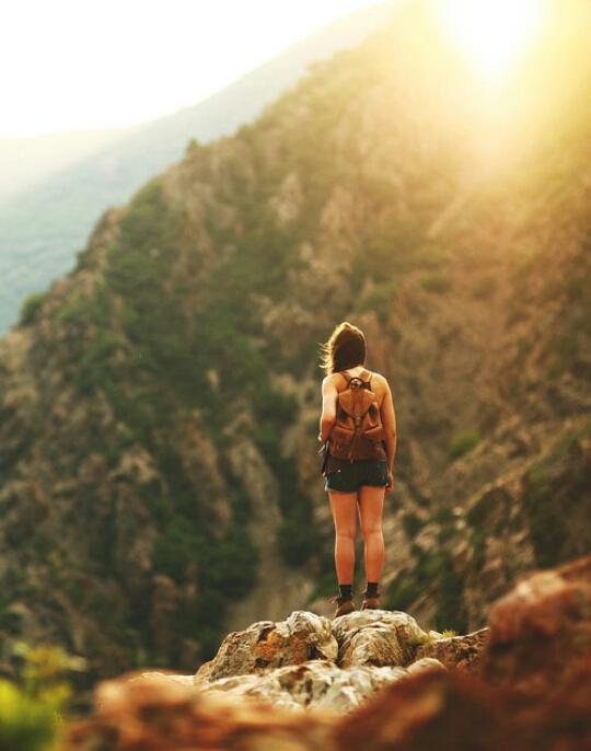 Chica parada sobre una montaña