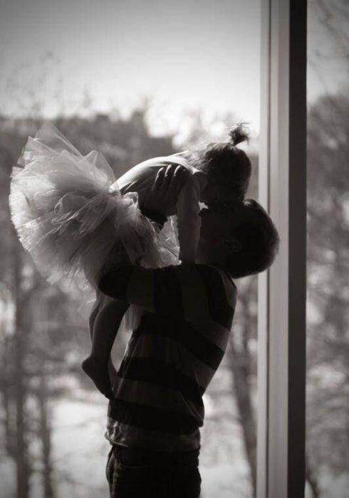 Padre cargando a su hija que practica ballet