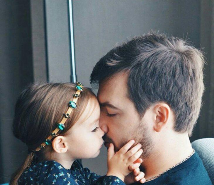 Padre besando en la frente a su hija