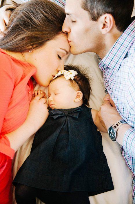 Padre besando a la mama de su bebé